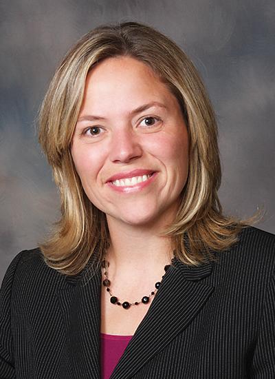 Dr. Jennifer Koontz in pinstripe suit jacket and maroon shirt - headshot
