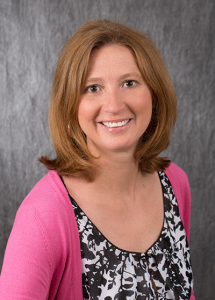 Dr. Stacy Sletcha in black and white shirt with pink sweater - headshot