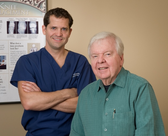 Dr. J. Scott Pigg & Dr. Charles C. Craig posing in front of knee replacement photo