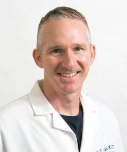 Dr. John Flesher in lab cot - headshot