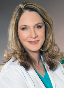 Dr. Stephanie Oberhelman in white lab coat and turquoise scrubs - headshot