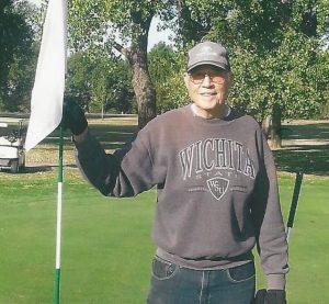 Man standing holding golf flag wearing Wichita State University sweatshirt and Toyota ball cap