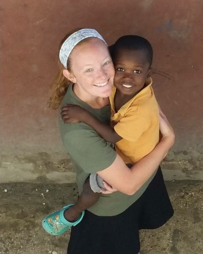 Olivia Miller hugging a kid from africa