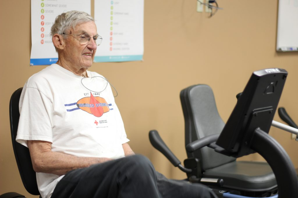 Older man experiencing cardiac rehab services by riding on stationay bike/elliptical