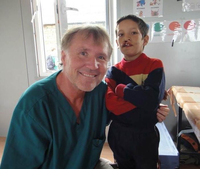Dr. Harry Wagner posing with child who has cleft palate