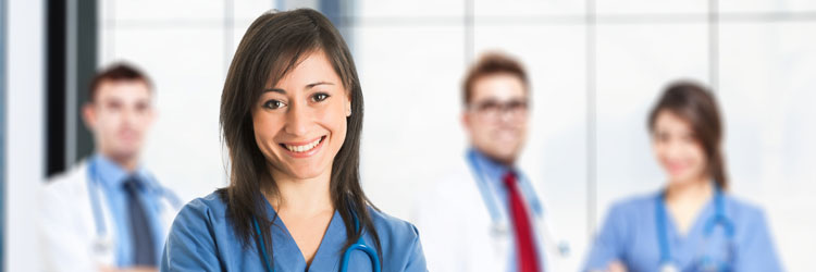 Woman in blue scrubs smile with three doctors blurred in background