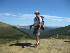Man with backpack and walking sticks standing on top of a mountain