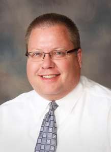 Dr. Kevin Brinker wearing white button up shirt and tie - headshot