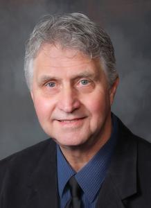 Dr. John Hart wearing suit and dark blue shirt - headshot