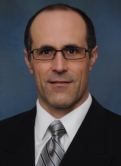 Dr. William Goodman wearing suit and gray tie - headshot