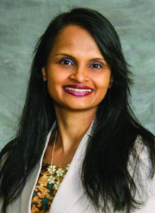 Dr. Shila Kshatriya wearing white jacket and gold and green shirt - headshot