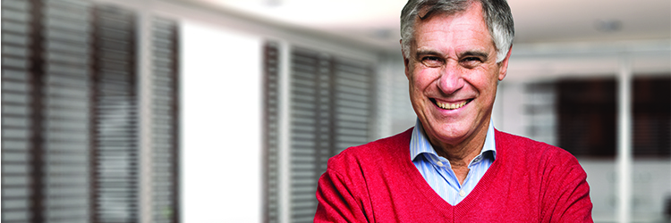 Man wearing red sweater and blue shirt smiling