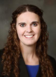 Dr. Jessica Brozek wearing black sweater and maroon shirt - headshot