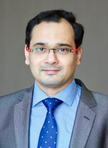 Dr. Abjiheet Kadam wearing dark gray suit with light blue shirt and tie - headshot