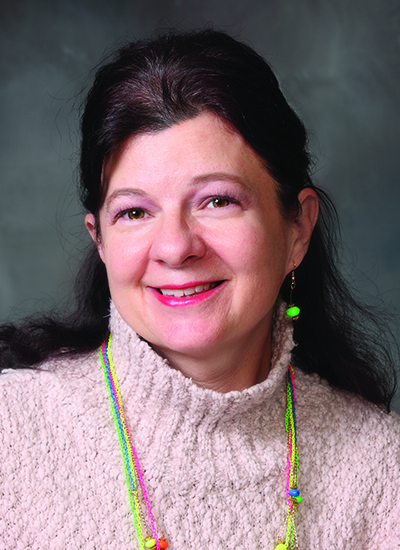 Dr. Yvonne Saunders-Teigeler wearing pink sweater in headshot