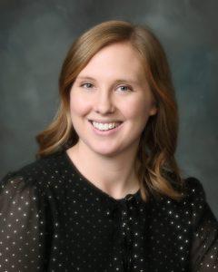 Justine Unruh, SLP wearing black shirt with silver polka dots - headshot