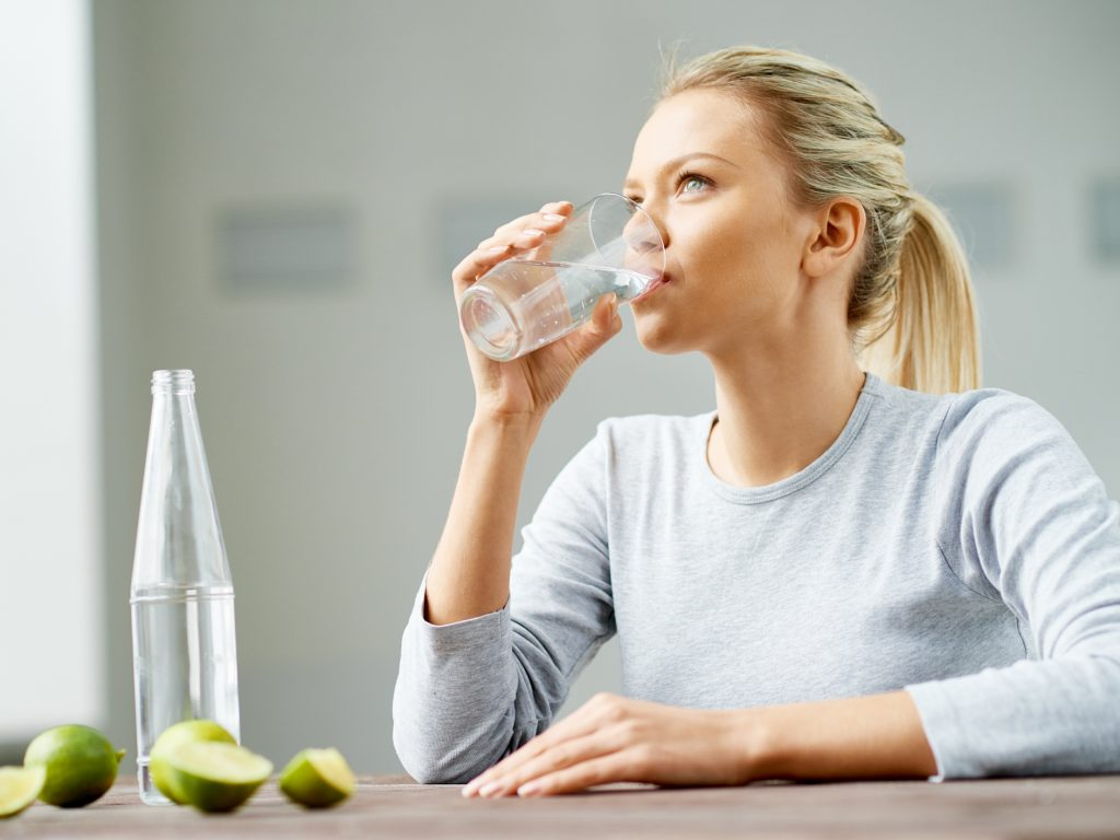 Woman with blonde hair and light gray shirt drinking a cup of water with lime slices sitting on the table in front of her