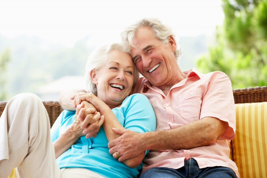 Old couple holding each other, sitting outside on patio smiling and laughing together