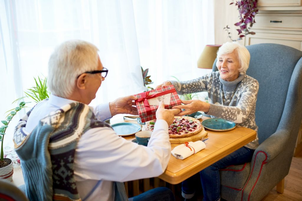 Old couple sitting at table eating dinner and exchanging gifts heart-healthy gift ideas for the one you love this Valentine's Day