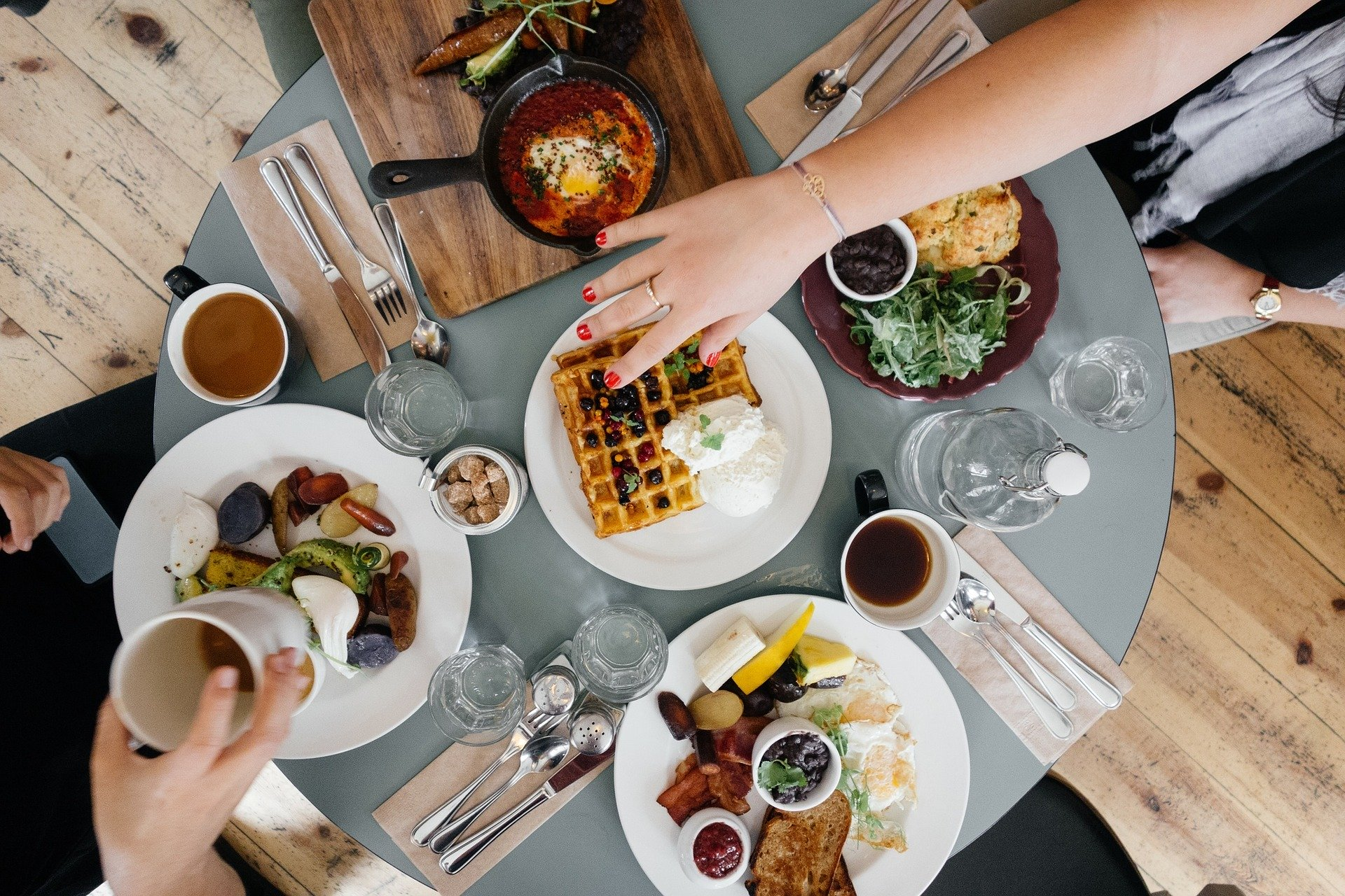 table full of breakfast items like waffles, coffee, omelets and sausage with two hands reaching across plates