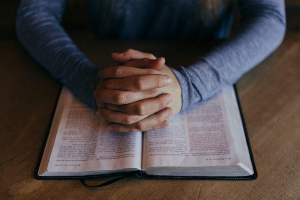 Praying hands over Bible/Quran/Koran