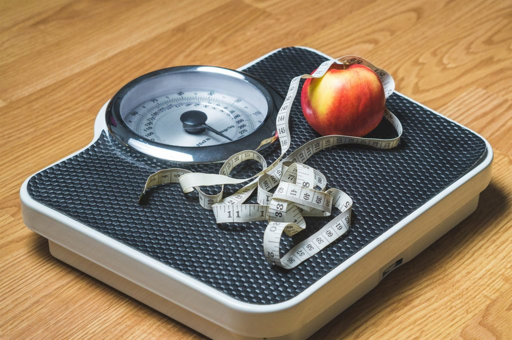 Scale with tape measure and apple sitting on it