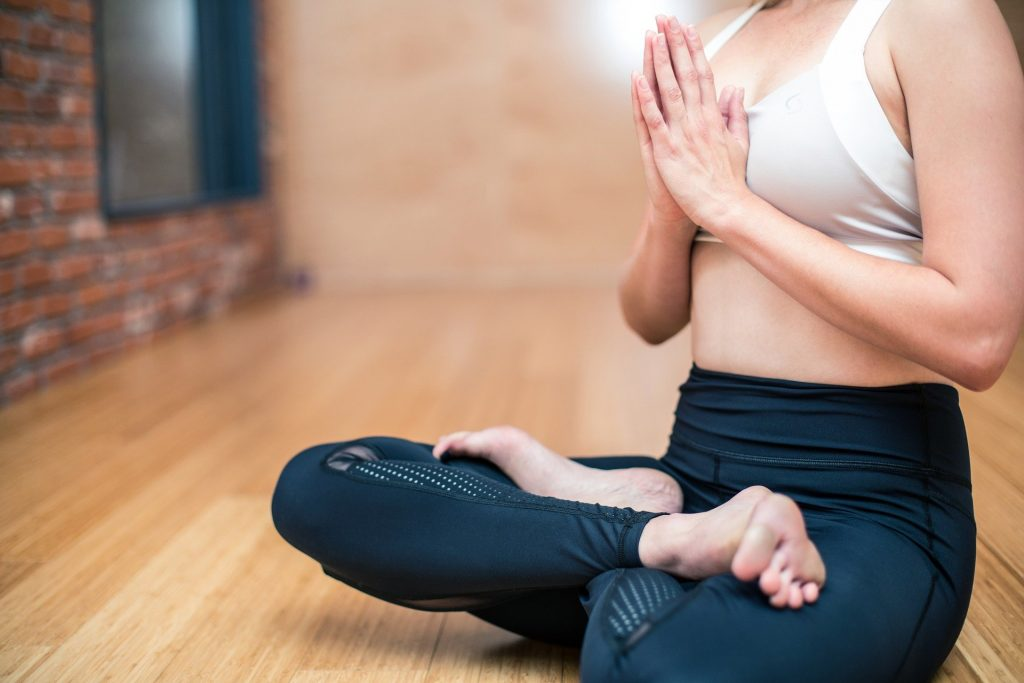 """Woman in yoga pants and top sitting criss cross applesauce with prayer hands in """"Namaste"""" pose."""