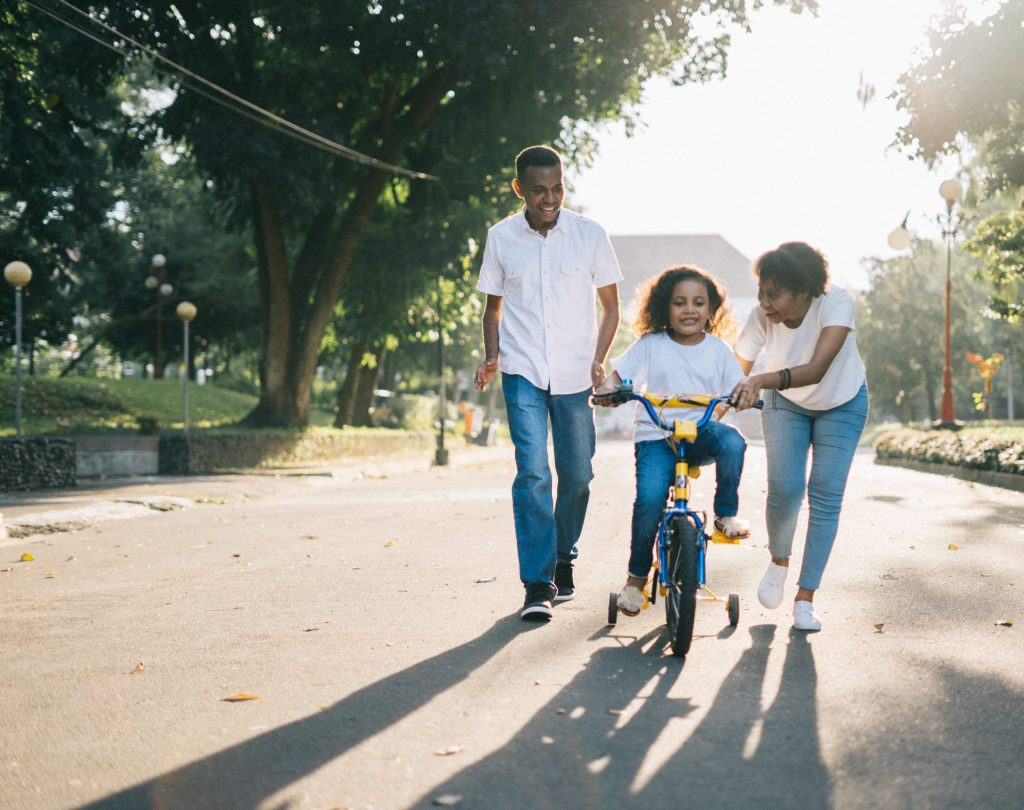 man-standing-beside-his-wife-teaching-their-child-how-to-ride-a-bike