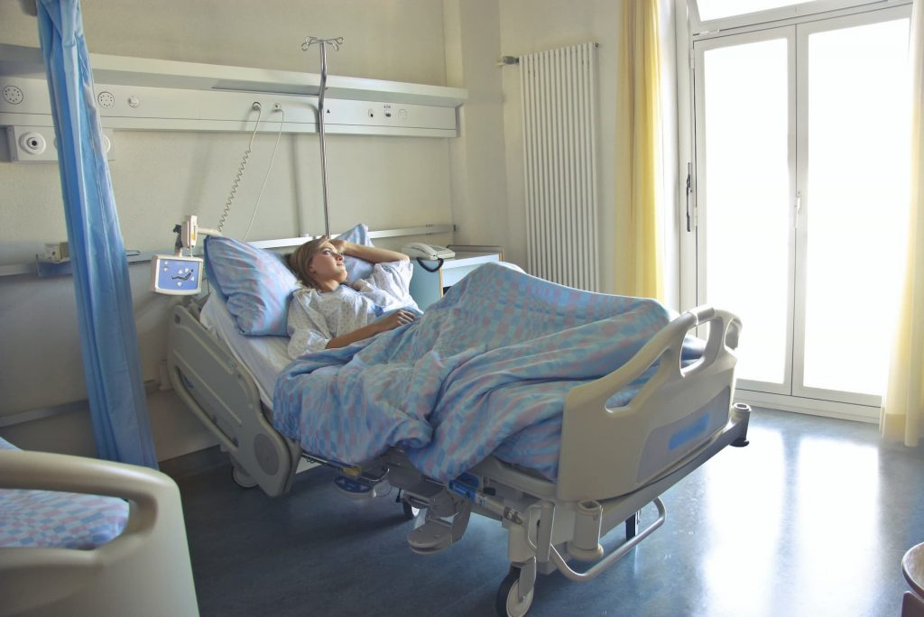 Woman lying in hospital bed staring out the window