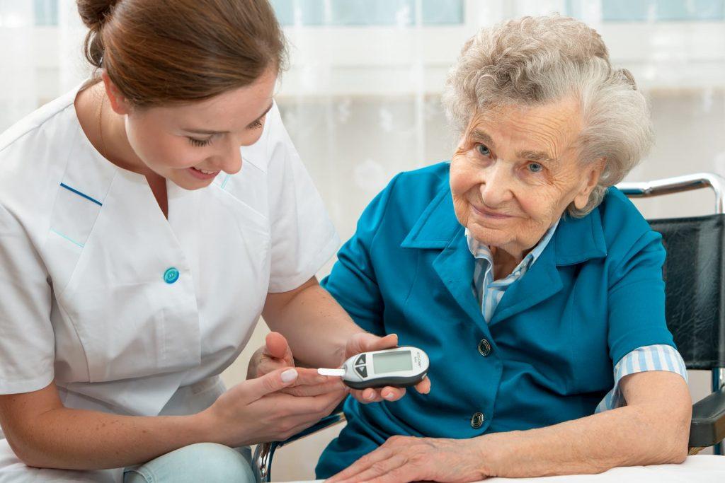 Nurse taking elderly woman's blood sugar with glucometer