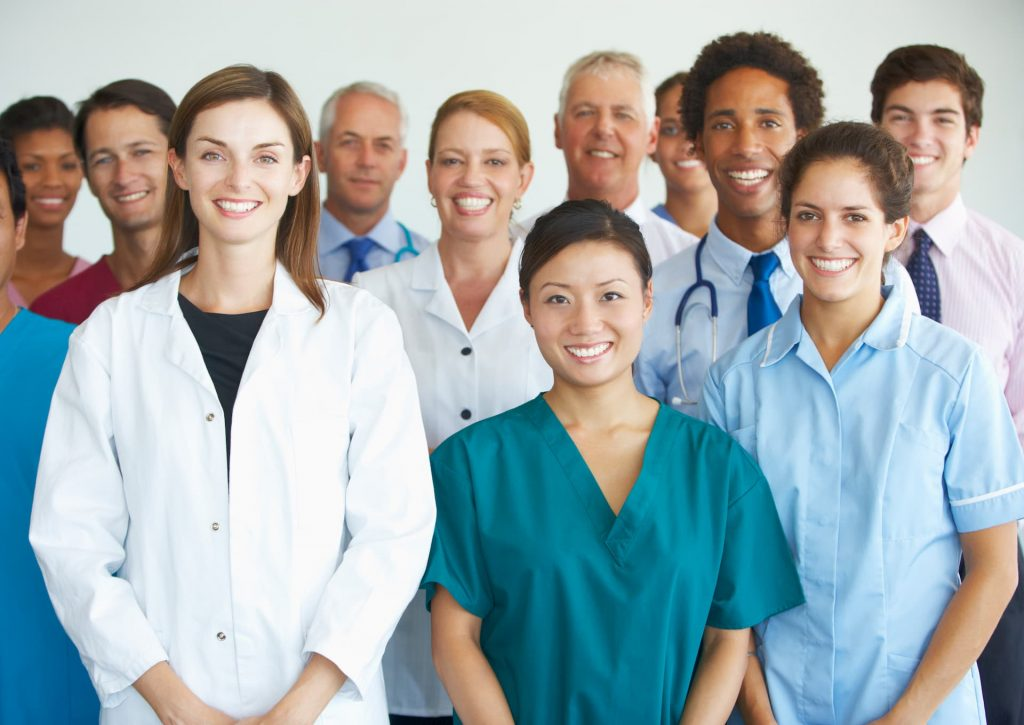 Group of diverse doctors, nurses and hospital staff standing in group photo