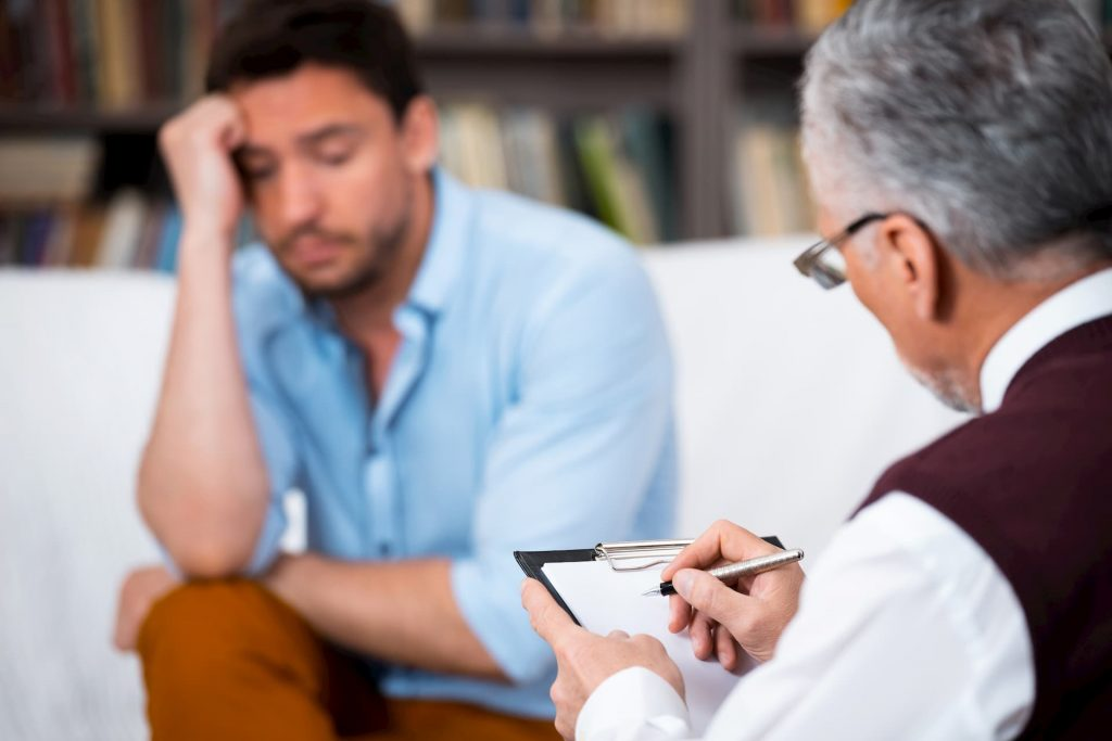 Man sitting with therapist talking about feelings