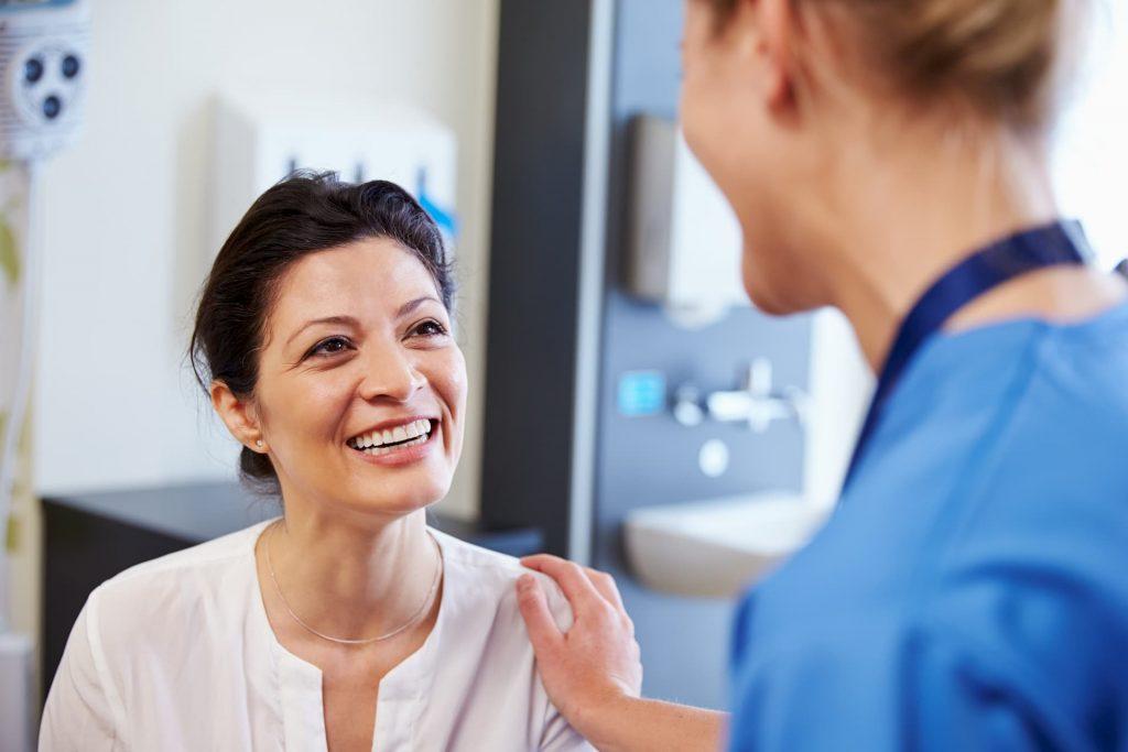 Hispanic patient smiling at nurse
