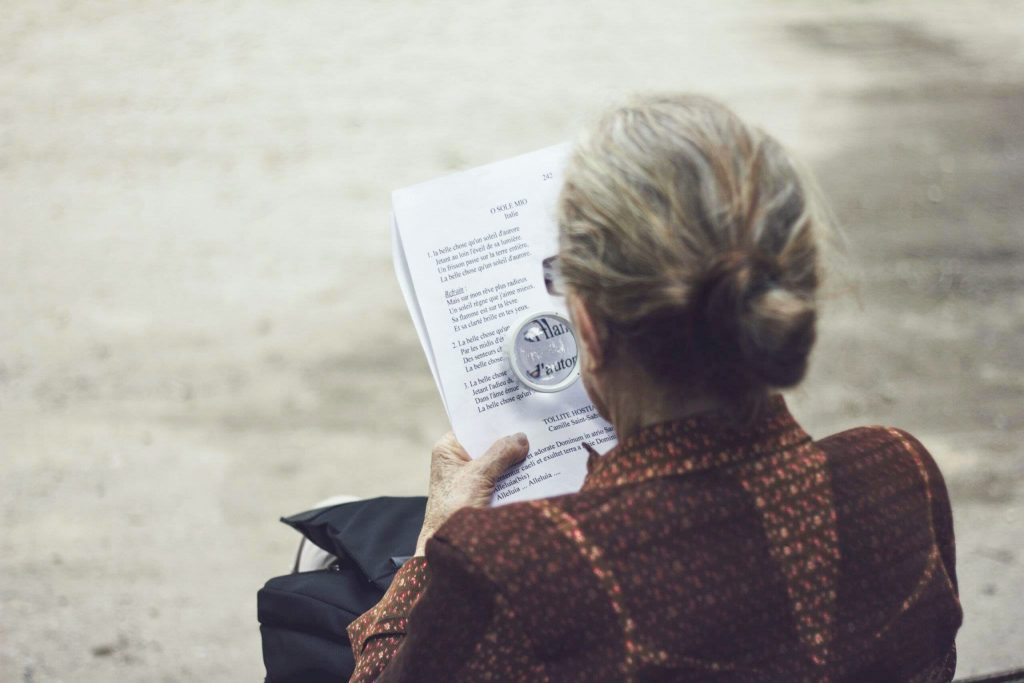 Woman using magnifying glass to read