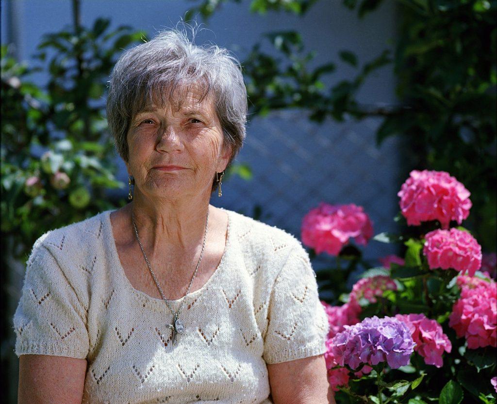 older woman sitting in front of flower garden