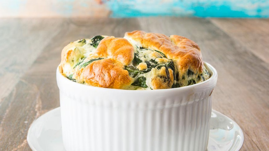 White souffle bowl with spinach souffle inside cooked to perfection