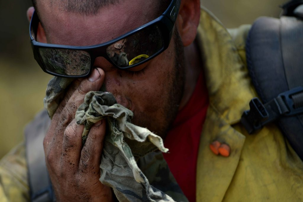 firefighter wiping sweat and soot away from his eye after fighting a fire
