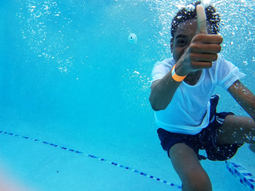 black kid swimming underwater giving thumbs up for swim safety