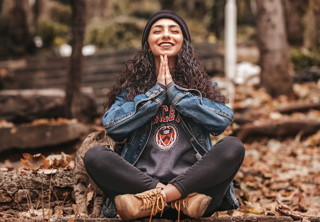 hispanic girl smiles and sits in indian style yoga pose with namaste hands