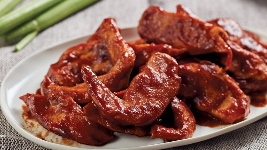 Plate of bbq chicken wings covered in glazed cherry sauce