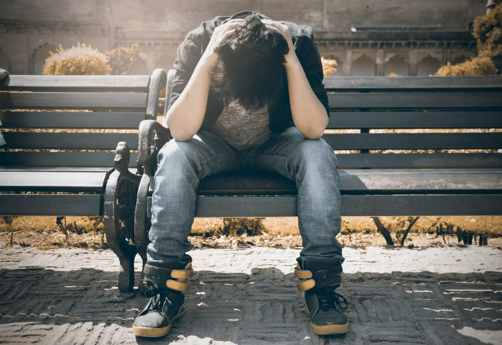 Teen with hands on head sitting on park bench - a sign of teen mental health.