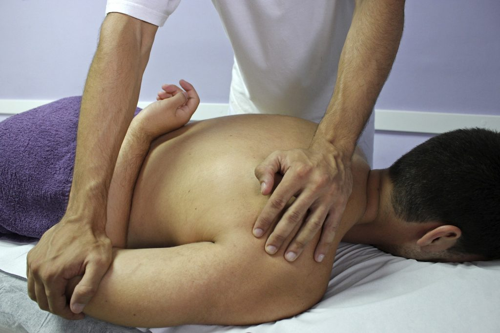 Doctor of Osteopathic Medicine (DO) adjusting a patient's shoulder to recude arm pain