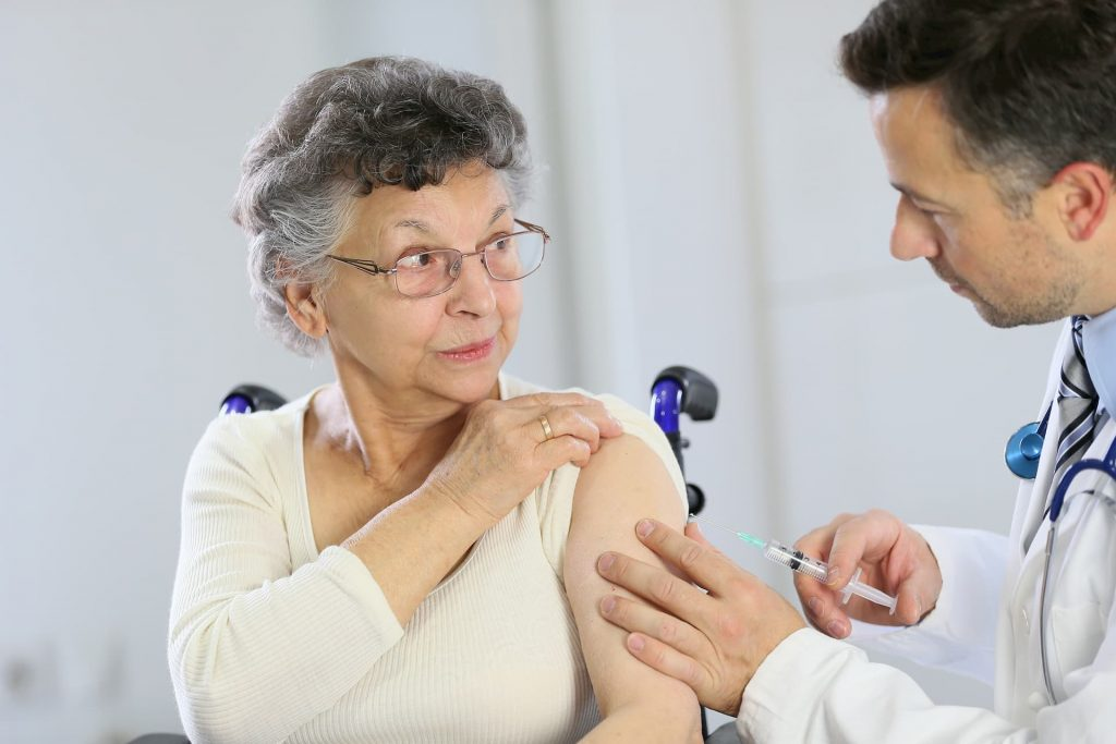 senior woman getting flu shot from doctor