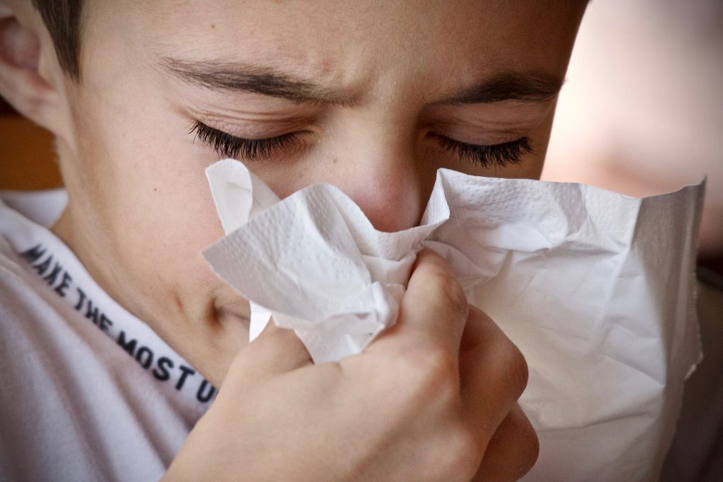 Young boy blowing nose into tissue