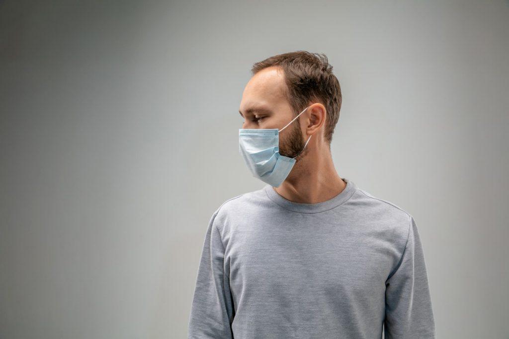 man wearing flu mask, gray shirt and background