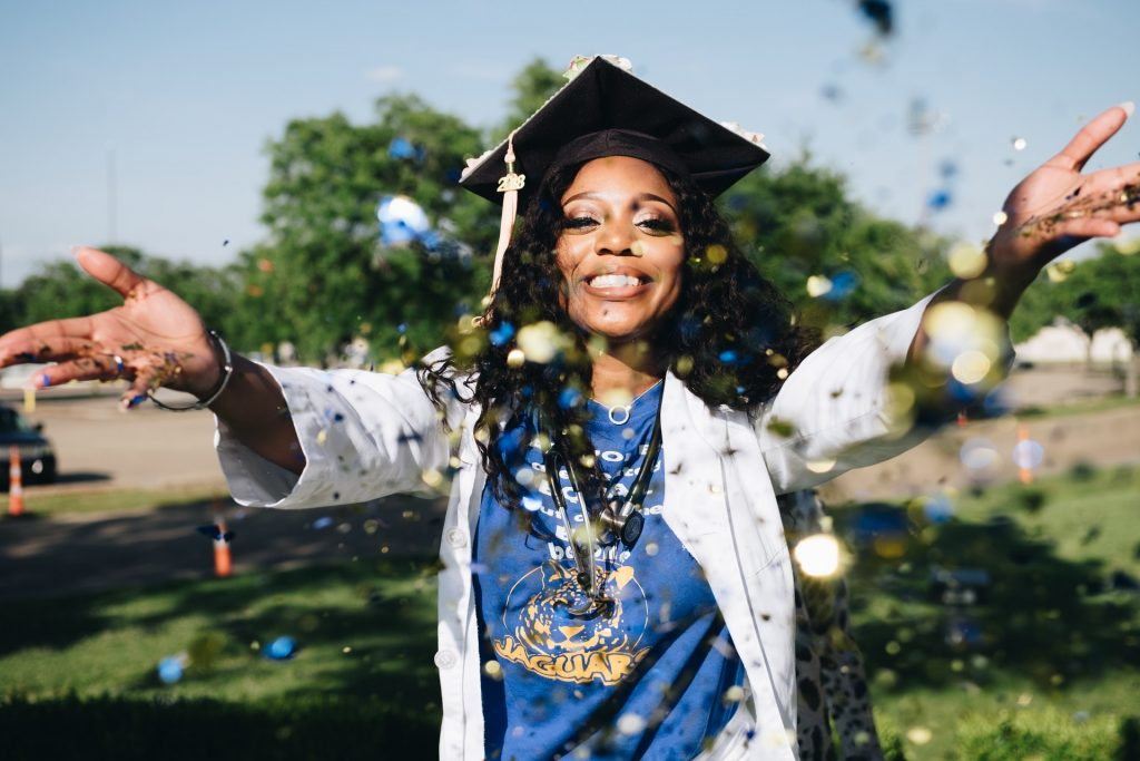 black nurse graduating from college, throwing confetti