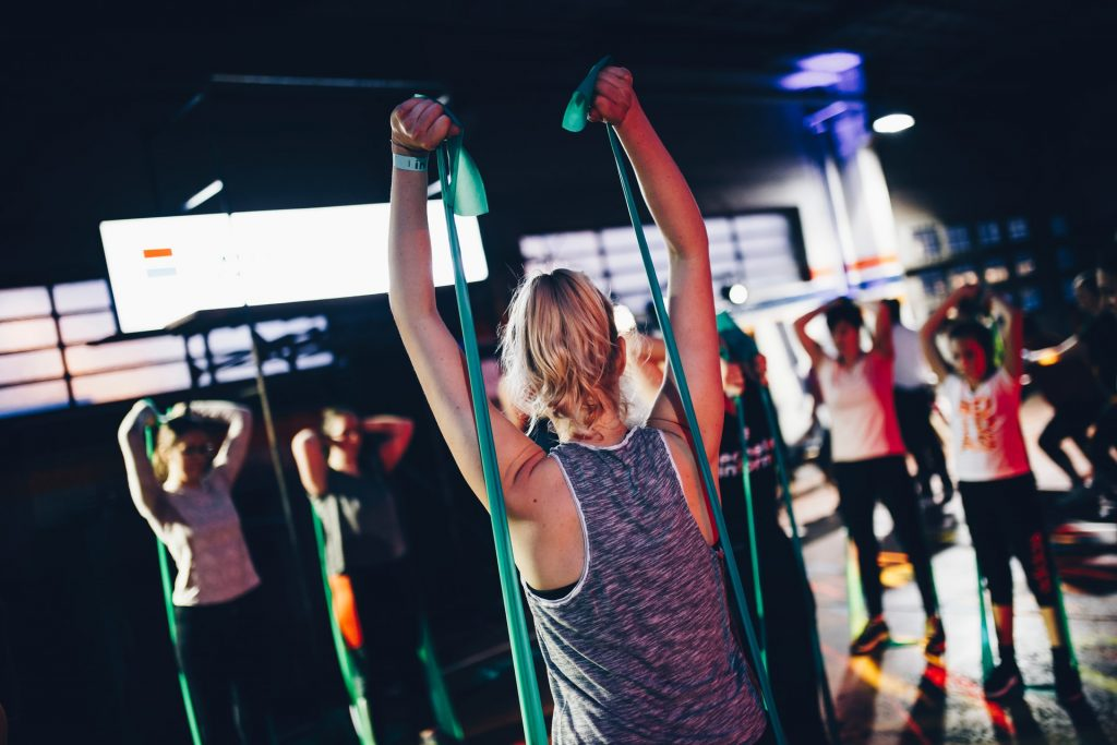 group women fitness class with stretch bands to get fit and help reduce the risk of breast cancer