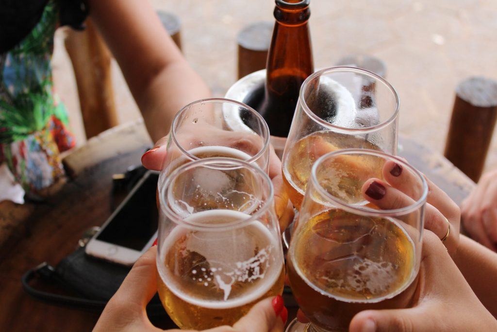four girl friends getting together to drink alcohol wine and beer to celebrate - don't drink more than one alcoholic beverage to limit your risk of breast cancer