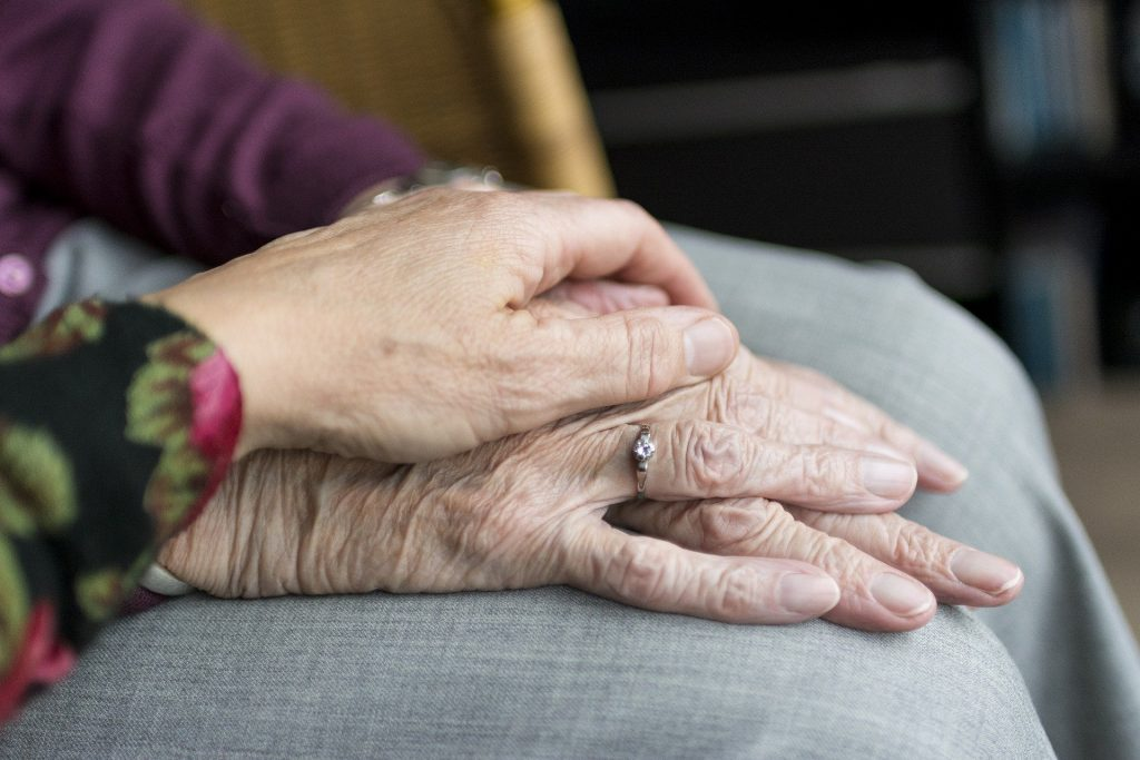 young daughter hold old mother's hands