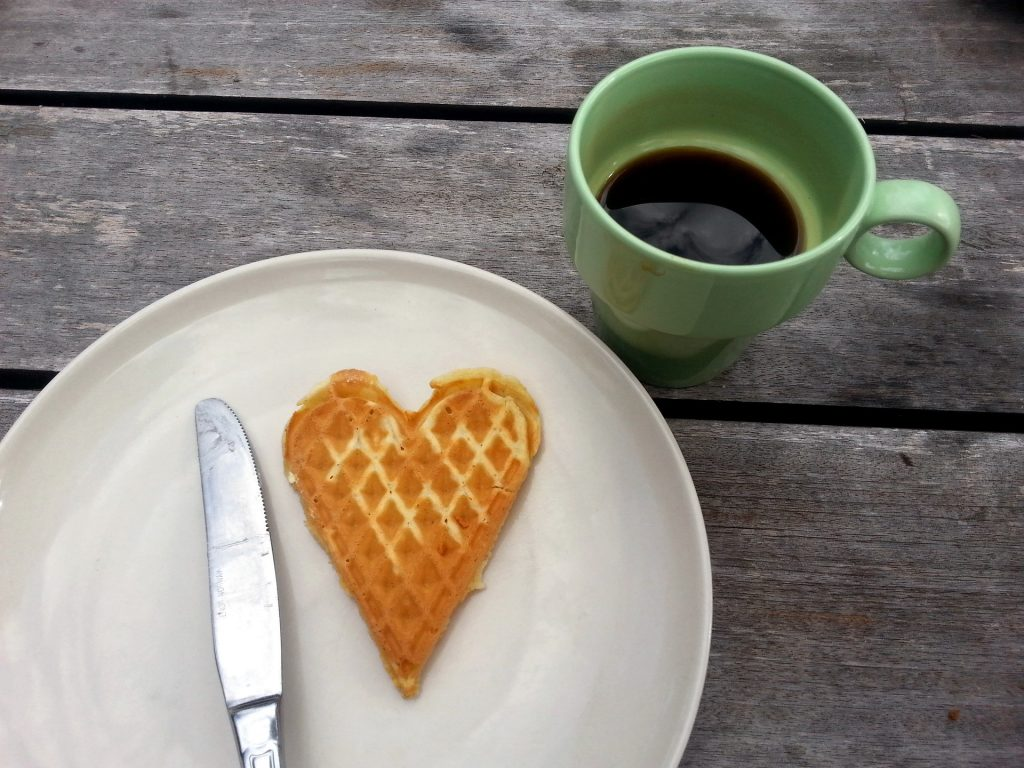 heart shaped waffle on plate with cup of coffee in green mug